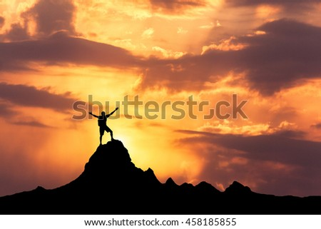 Landscape with silhouette of a standing happy man with backpack and raised-up arms on the mountain peak on the background of cloudy sky at colorful sunset in summer. Travel, Climbing, Trekking.