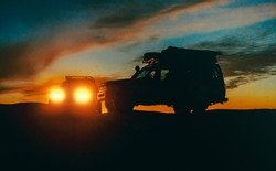 Landscape with silhouettes of two off-road cars at sunset, low light photo. Traveling by car - idea for your adventure in wildlife, scientific expedition or extreme travel on a SUV automobile.