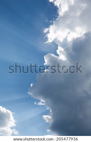 Landscape with sun rays through white clouds on blue sky. Vertical photo