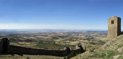 Landscape with the walls and Romanesque Albarrana Tower of the Castle of Loarre and the flat Valley of Huesca in the rear. Aragon. Spain.