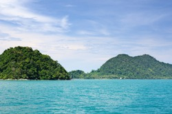 Landscape with turquoise tropical sea, dark blue sky with white clouds and tropical Koh Chang island on horizon in Thailand