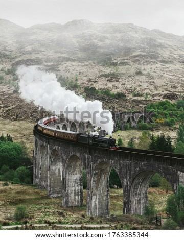 Landscape with viaduct and train. Glenfinnan viaduct in scotland. Retro steam locomotive steam train railway in the mountains.