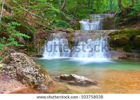 landscape with waterfall in green forest