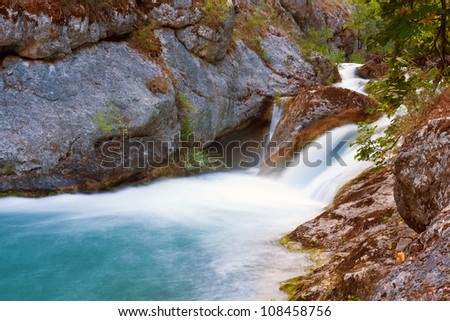 Landscape with waterfall on mountain river