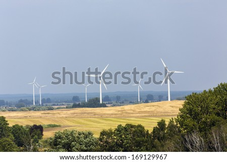 landscape with wind turbines forest and fields.