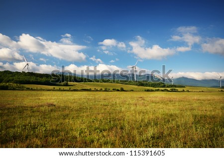 Landscape with wind turbines under blue cloudy sky, mountains at background
