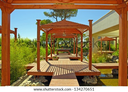 Landscape with wood pavilion, deck and tropical plants in summer resort - stock photo