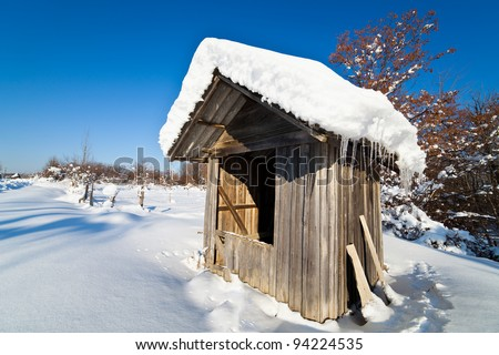 Landscape with wooden shack in the snow, under blue sky