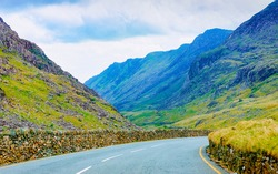 Landscape without Cars in empty road in Snowdonia of UK. Vacation trip on highway with nature. Scenery with drive on Holiday journey for recreation. Motion ride in Europe. No Transport