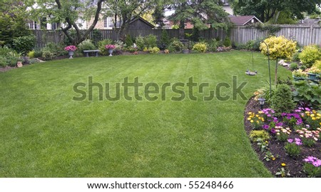 landscaped backyard surrounded by wooden fence