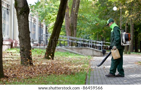 Landscaper Worker cleaning foot way in park from Dead Leaves using gas powered Leaf Blower Stock photo ©