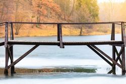 Landscapes, objects, beauty of nature concept. Old, wooden, small bridge on frozen lake, sunny chilly day.