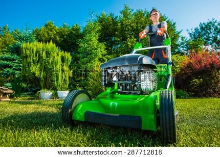 Landscaping Business. Gardener Mowing Backyard Lawn. Green Gasoline Lawn Mower