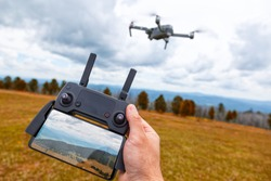Landscaping on a quadcopter. A young man holds in his hand a quadcopter control panel with a monitor and an image of mountains