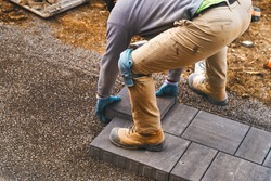 Landscaping paver worker laying paving stones on sandy ground of construction patio site during spring summer. Contractor wearing safety protective cloth, gloves and knee pads for installation work.