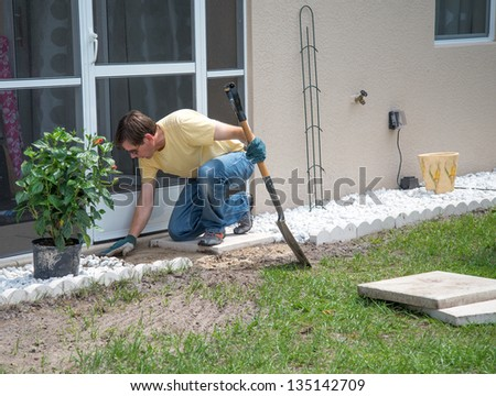 Landscaping Work - A man working outdoors.  He is using a shovel to level the dirt to place concrete patio slabs in the landscaping near the door to the house.