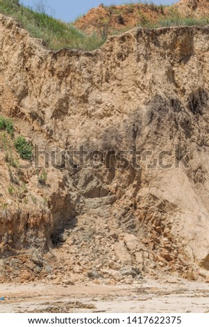 Landslide zone on Black Sea coast. Rock of sea rock shell. Zone of natural disasters during rainy season. Large masses of earth slip along slope of hill, destroy houses. Landslide - threat to life #1417622375