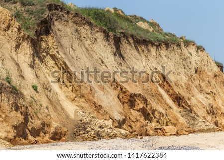 Landslide zone on Black Sea coast. Rock of sea rock shell. Zone of natural disasters during rainy season. Large masses of earth slip along slope of hill, destroy houses. Landslide - threat to life #1417622384