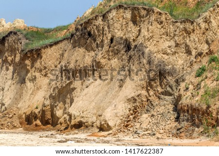 Landslide zone on Black Sea coast. Rock of sea rock shell. Zone of natural disasters during rainy season. Large masses of earth slip along slope of hill, destroy houses. Landslide - threat to life #1417622387