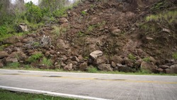 Landslides and rockfalls on the road in the mountains. Mud and rocks blocking the road.Destroyed rural road landslide damaged in powerful flood. Collapsed on the mountain. Philippines, Camiguin.