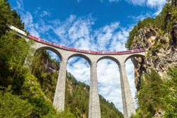 Landwasser Viaduct in Filisur, Switzerland. It is landmark of Swiss Alps. Red express train runs on high bridge in Alpine mountains. Scenic view of famous railway in summer. European travel concept.