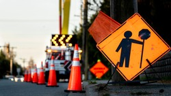 Lane closure on a busy road due to maintenance, signs detour traffic temporary street work orange lighted arrow, barrels and cones.