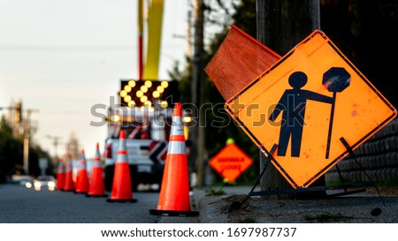 Lane closure on a busy road due to maintenance, signs detour traffic temporary street work orange lighted arrow, barrels and cones. ストックフォト ©
