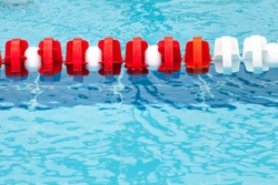 Lane divider, pool marker lines. Line dividers pool. Blue, red and white. Blue clean water. Horizontal background.