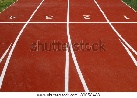 Lanes of a red race track with numbers for athletic venue
