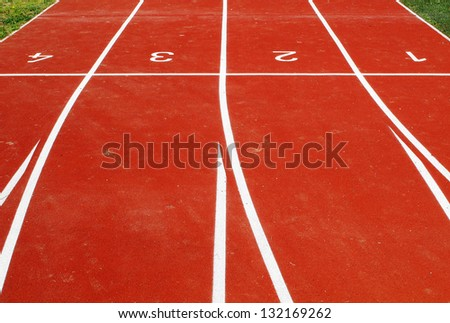 Lanes of a red race tracks with numbers for athletic venue