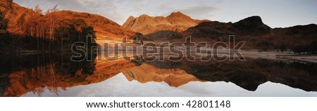 Langdale Pikes reflected in Blea Tarn at dawn in the English Lake District