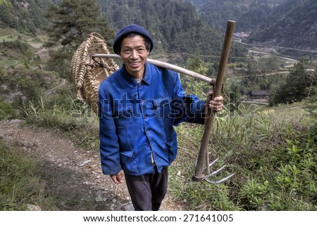 Langde Village, Guizhou, China - April 15, 2010: Chinese man, a villager, farmer, a peasant in a knitted cap and a blue work jacket, carries on the shoulder yoke with a wicker basket and a fork hoe.