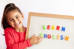 Language education concept. Learn English. Do you speak English. Cute little child girl with letters on the blackboard. English language school. English for children.