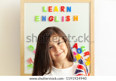 Language education concept. Learn English. Do you speak English. Cute little child girl with colored letters on the blackboard. English language school. English for children.
