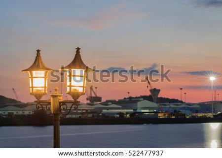 Lantern a lamp with a background sunset on the sea with beautiful sky and clouds in the evening twilight. #522477937
