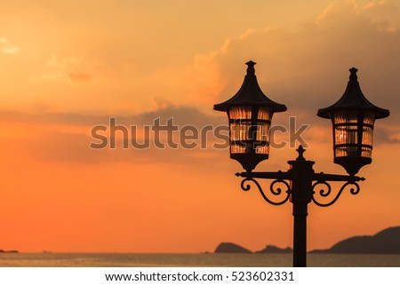 Lantern a lamp with a background sunset on the sea with beautiful sky and clouds in the evening twilight. #523602331