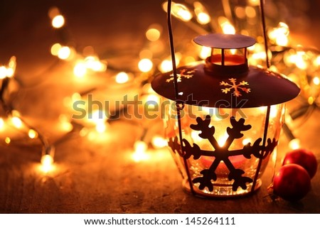 Lantern and Christmas lights burning in dark.