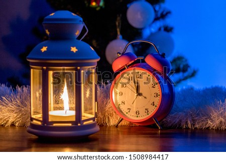 Lantern and clock under the Christmas tree on the eve of New Year's Eve