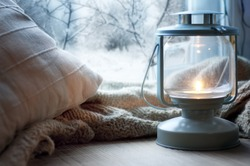 lantern and pillows on windowsill with winter view