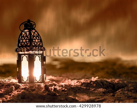 lantern lighted inside by candle and shining on sand floor playground, children play with it in Ramadan night, also known and called as Ramadan lantern