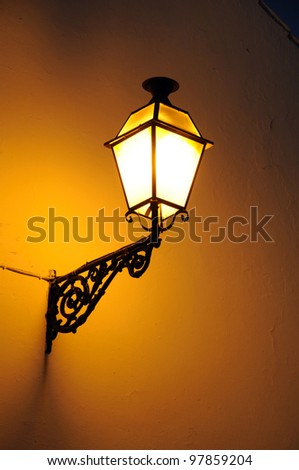 Lantern on a wall in the Plaza de Santa Maria at night, Antequera, Malaga Province, Andalucia, Spain, Western Europe.