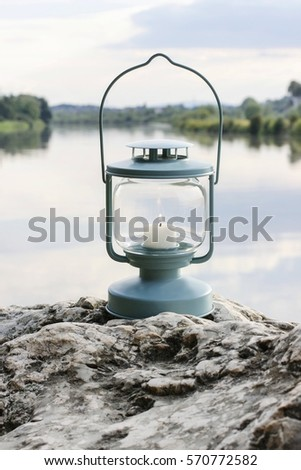 Lantern on the rock, lake in the background.