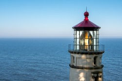 Lantern Reflects in Heceta Head Lighthouse with calm Pacific ocean in background