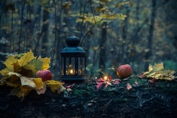 Lantern with a candle in the autumn forest, surrounded by candles and red apples.