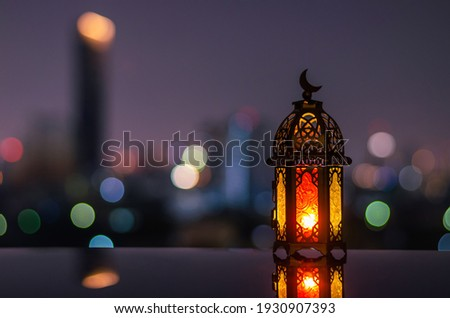 Lantern with dusk sky and city bokeh light background for the Muslim feast of the holy month of Ramadan Kareem.