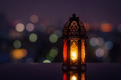 Lantern with night sky and city bokeh light background for the Muslim feast of the holy month of Ramadan Kareem.