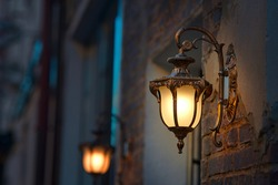 Lantern with yellow warm light on facade of building. Twilight on city street, building illumination. Retro lantern lighting, warm light glow. Street lights, illumination and vintage lantern