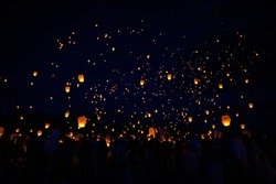 Lanterns are released into the night sky.