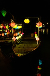 Lanterns light up night on boats in Hoi An, Vietnam. Famous for lantern festival along river. Hoi An is a UNESCO World Heritage Site and one of the most visited cities in Vietnam by tourist.