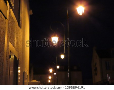 Lanterns with orange light at night against black sky and village house in Arromanches, Normandy, France #1395894191